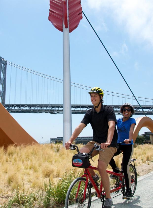 Tandem team riding in front of Cupid's Span and the Bay Bridge on a beautiful clear day!