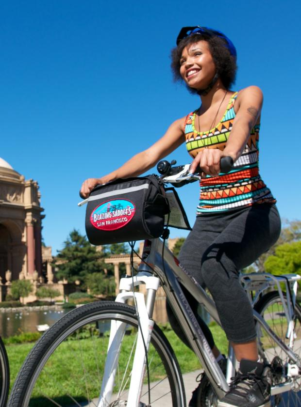Couple smiling and biking in front of the Palace of Fine Arts