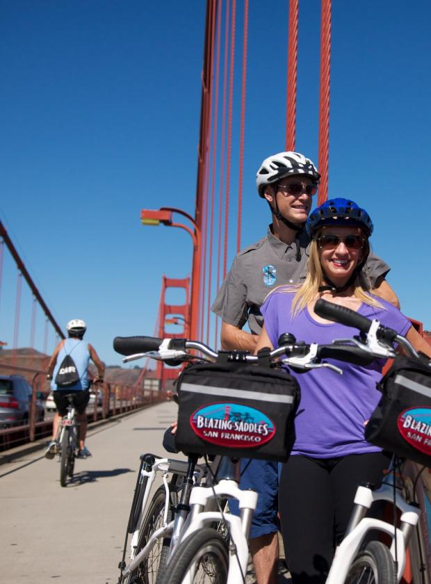 Happy couple ejoying the sight on the Golden Gate Bridge before continuing their ride to Sausalito