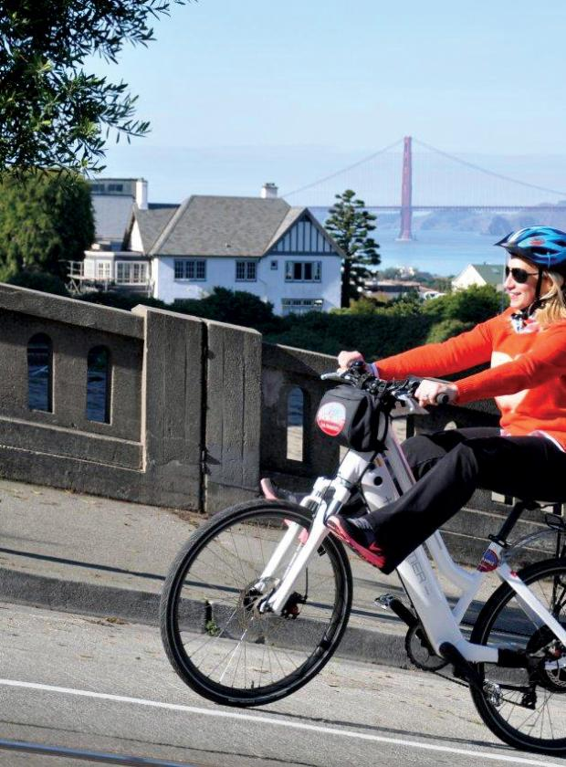 Woman riding up the hilly streets of San Francisco with ease on an Electric Bike