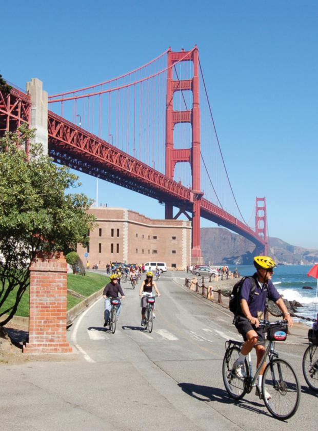 Guided bike tour riding under the Golden Gate Bridge near historic Fort Point
