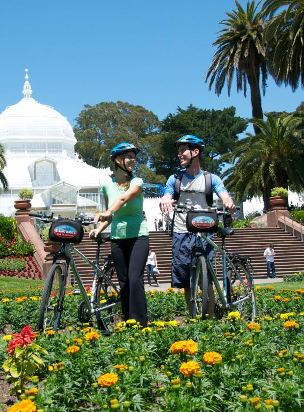 Bikers exploring the gardens in front of the Historic Conservatory of Flowers in Golden Gate Park