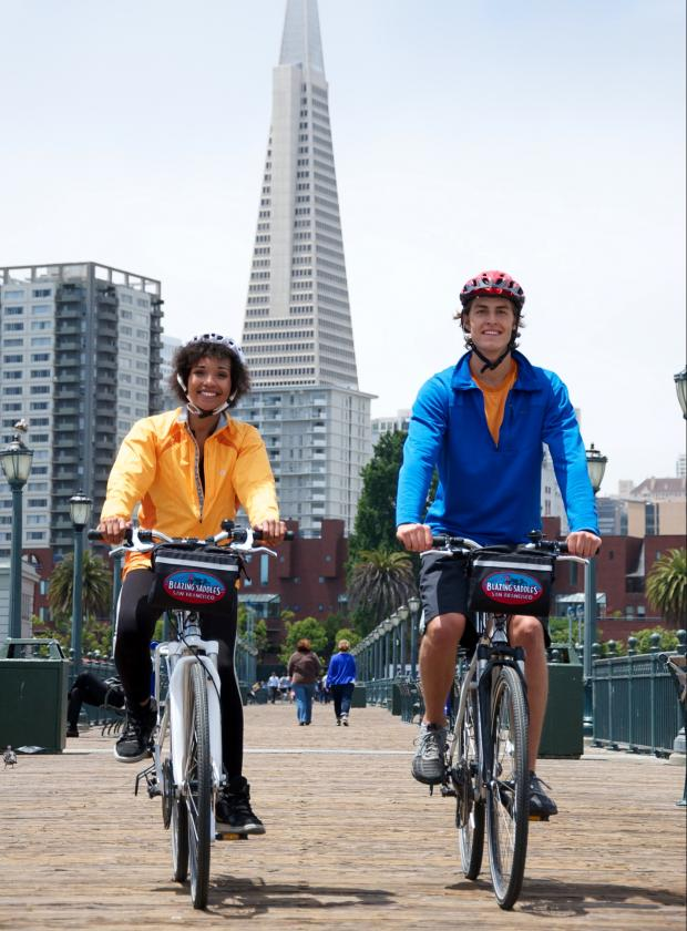 Couple biking along the piers past the Transamerica Pyramid and San Francisco's Financial District