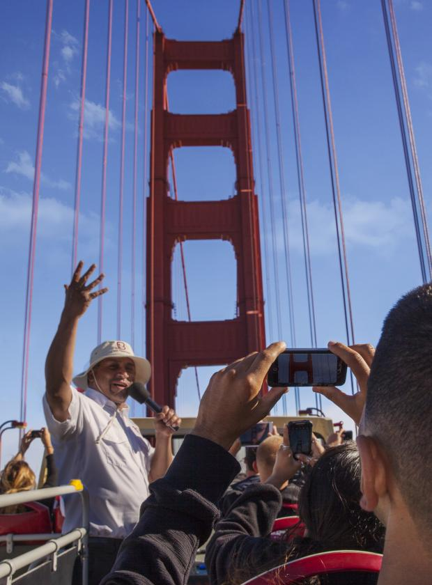 Double-decker bus crossing the Golden Gate Bridge while a tour guide narrates its history