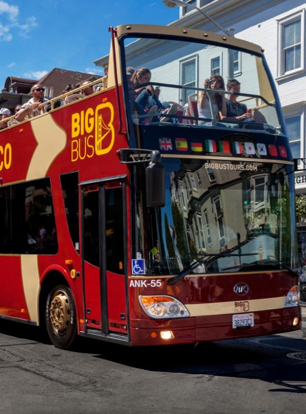 Visitors enjoying the sights and sound of San Francisco on an open-top, double-decker bus