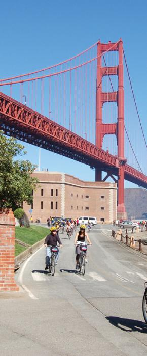 Bike riders on a guided tour departing historic Fort Point underneath the Golden Gate Bridge