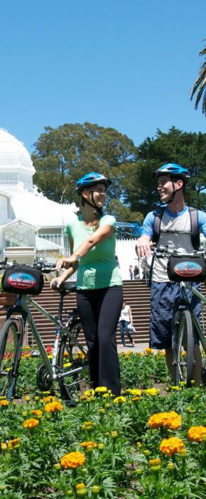 Two bikers exploring the gardens in front of the Conservatory of Flowers in Golden Gate Park