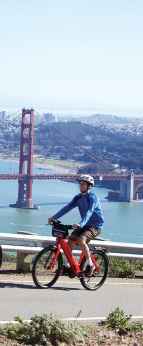 Couple of bikers on Hawk Hill in the Marin Headlands with stunning views of the Golden Gate Bridge and San Francisco
