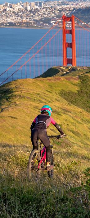 Mountain biker conquering the off-road trails in the Marin Headlands with incredible views of the Golden Gate Bridge and San Francisco